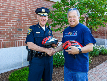 Attorney David W. White of Breakstone, White & Gluck delivers free children's bicycle helmets to Norwood Police Chief William G. Brooks.
