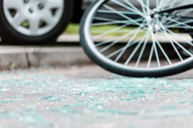 Bicycle wheel and shattered glass after car hits bicyclist at Boston intersection