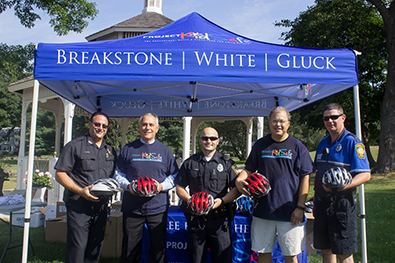 Attorney David W. White and Ronald E. Gluck of Breakstone, White & Gluck with members of the Dedham Police Department at the Dedham Bike Rodeo. Breakstone, White & Gluck donates bicycle helmets to children there each year through our Project KidSafe campaign.