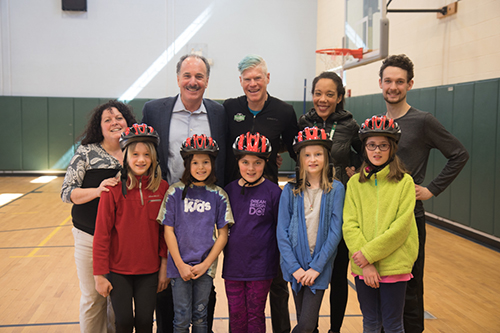Boston attorney Marc Breakstone with students, volunteers and participants at Pierce School in Arlington, where the law firm of Breakstone, White & Gluck gave away free bicycle helmets to students as part of its Project KidSafe campaign.