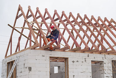 Roofer putting beams on a house frame